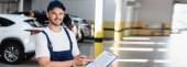 panoramatický koncept šťastný mechanik v uniformě a čepici držící podložku se smluvním nápisem a perem v blízkosti automobilů