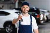 veselý mechanik v uniformě a čepici držící klíč od auta