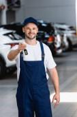 Lächelnder Mechaniker in Uniform und Mütze mit Autoschlüssel in der Werkstatt