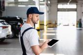 Mechaniker in Uniform und Mütze mit digitalem Tablet mit leerem Bildschirm in der Werkstatt