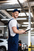 cheerful mechanic in uniform and cap holding digital tablet with blank screen in workshop