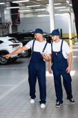 šťastný mechanik v uniformě držící digitální tablet a ukazující prstem na auto poblíž spolupracovníka v dílně