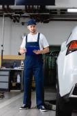 Mechaniker in Uniform hält Klemmbrett beim Blick auf Auto