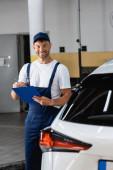 veselý mechanik v čepici drží schránku v blízkosti moderního auta