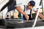 selektivní zaměření mechanika v montérkách upevnění auta u spolupracovníka na čerpací stanici