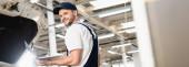 Panoráma lövés mosolygós autószerelő gazdaság laptop töltőállomáson