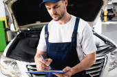 Automechaniker schreibt auf Klemmbrett nahe geöffneter Motorhaube von Auto an Tankstelle