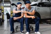 Usmívající se automechanik dává pěstí nárazu do kolegy v blízkosti auta na čerpací stanici