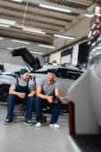 Selektivní zaměření šťastné automechaniky sedí a drží papírový kelímek a latexové rukavice na čerpací stanici