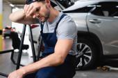Unavený automechanik s rukou u čela sedí u aut na čerpací stanici