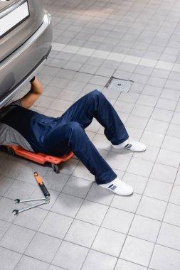 Mechanic in uniform lying under car near metallic tools stock vector