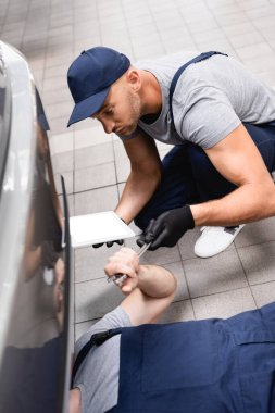 Selective focus of mechanic in uniform holding digital tablet while giving wrench to coworker lying and repairing auto stock vector