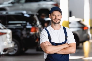 Happy mechanic in uniform and cap standing with crossed arms in car service stock vector