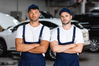 Handsome mechanics in uniform and caps standing with crossed arms in car service stock vector
