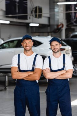 Happy mechanics in uniform and caps standing with crossed arms in car service stock vector