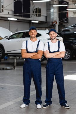 Cheerful mechanics in uniform and caps standing with crossed arms in car service stock vector