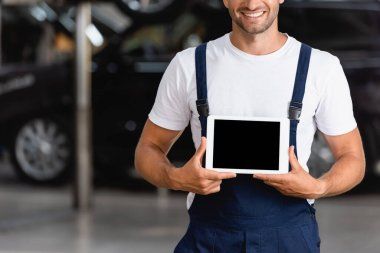 Cropped view of happy mechanic in overalls holding digital tablet with blank screen in car service stock vector