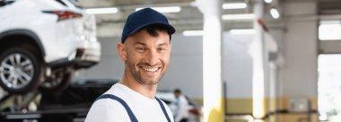 Panoramic shot of happy mechanic in cap looking at camera stock vector