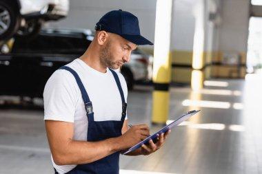 Handsome mechanic in uniform holding clipboard stock vector