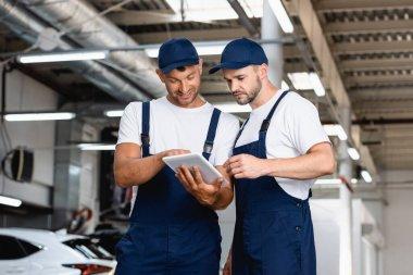 Happy mechanics in uniform looking at digital tablet in workshop stock vector