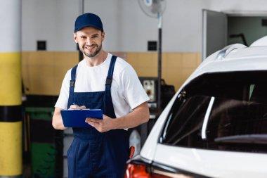 Happy mechanic in uniform holding clipboard near modern car stock vector