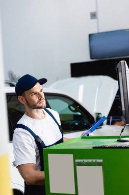 Handsome mechanic in cap looking at computer monitor in workshop stock vector