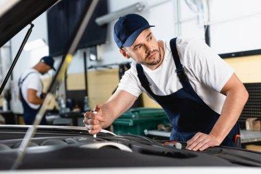 Selective focus of mechanic in cap repairing auto near coworker in workshop stock vector