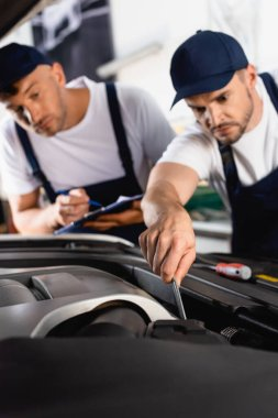 Selective focus of mechanic in uniform repairing car near coworker with clipboard and pen stock vector