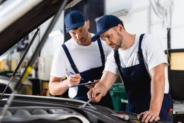 Selective focus of mechanic in uniform fixing car near coworker with clipboard and pen stock vector