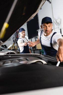 Selective focus of mechanic in cap giving screwdriver to coworker repairing car in workshop stock vector
