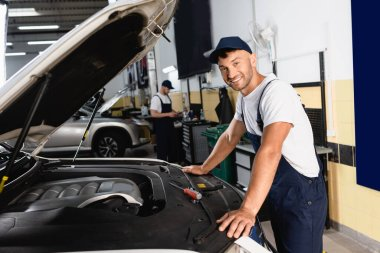 Selective focus of happy mechanic in cap smiling near car and coworker in workshop stock vector