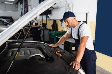 Selective focus of mechanic in cap looking at car near coworker in workshop stock vector