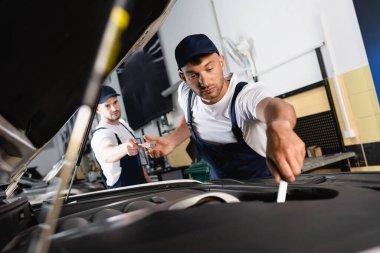 Selective focus of mechanic in cap giving screwdriver to handsome coworker repairing car in workshop stock vector
