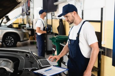 Selective focus of auto mechanic using laptop on car near clipboard at service station stock vector