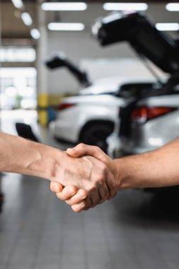 Selective focus of handshake gesture of men at service station stock vector