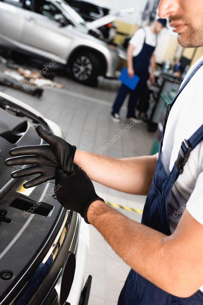vista ritagliata del meccanico in uniforme indossando guanti di lattice vicino all'auto in officina