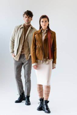Full length view of young, stylish couple in trendy autumn clothes posing on grey stock vector