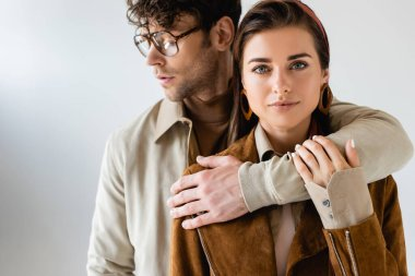 Stylish man in eyeglasses hugging stylish woman looking at camera on grey stock vector