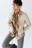 trendiger Mann in Herbstkleidung sitzt auf einem Hocker, die Hände in den Taschen und schaut weg auf grau