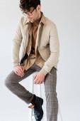 schöner Mann in stylischer Herbstkleidung sitzt isoliert auf einem Schemel in grau