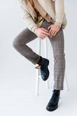 Ausgeschnittene Ansicht eines trendigen Mannes in grauer Hose und schwarzen Stiefeln, der auf einem Schemel auf grau sitzt