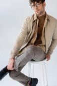 stilvoller, selbstbewusster Mann, der auf einem Hocker sitzend in die Kamera blickt und das Bein isoliert auf grau berührt