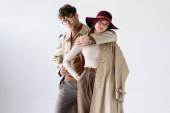 stylový muž objímání trendy žena při pózování v podzimním oblečení izolované na šedé