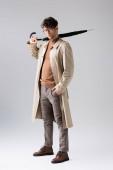 pohled na trendy muže držícího složený deštník při pohledu na fotoaparát na šedé