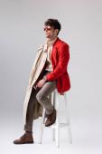 Fotografie gutaussehender, stylischer Mann mit Trenchcoat auf der Schulter, der auf einem Schemel sitzt und wegschaut auf Grau