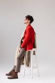 Seitenansicht eines jungen Mannes im trendigen Herbst-Outfit, der wegschaut, während er sich auf einen Schemel in Grau lehnt