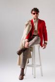 schöner, selbstbewusster Mann in stylischer Herbstkleidung, der auf einem Schemel auf grau sitzend das Bein berührt
