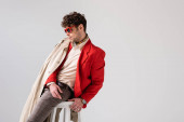 Fotografie schöner Mann in trendiger Herbstkleidung sitzt isoliert auf einem Schemel in grau