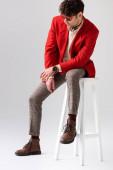 Trendsetter in rotem Blazer und Sonnenbrille sitzt auf einem Hocker mit gesenktem Kopf auf grau