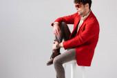 stylischer Mann in rotem Blazer und Sonnenbrille, der auf einem Stuhl sitzend, isoliert auf grau, das Bein berührt